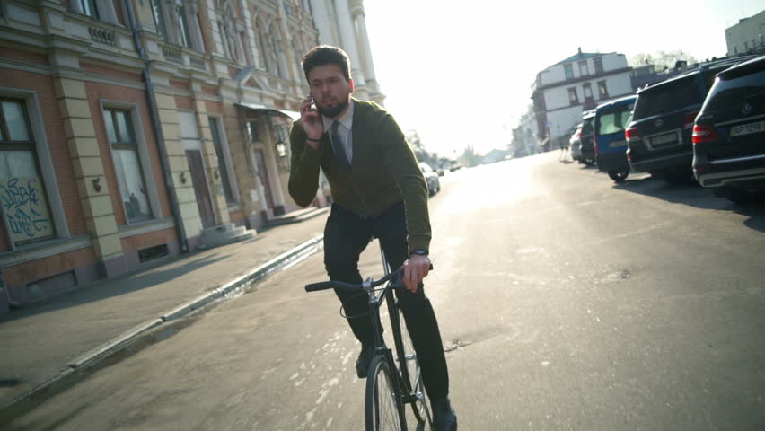 handsome man rides a bike and talks on the phone slow motion #16019983