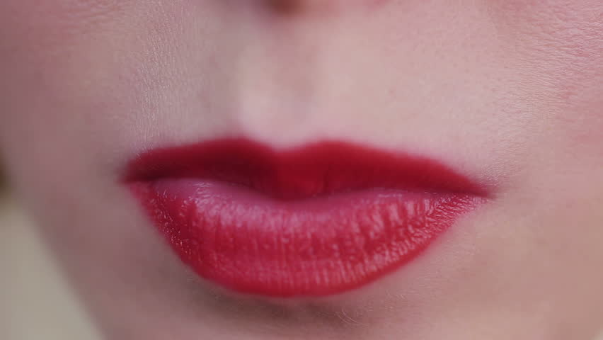 Ill-mannered female chewing gum and blowing a bubble, closeup of beautiful lips