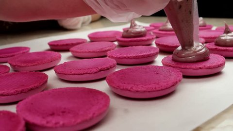 Making pink Macarons, add filling from the cooking bag