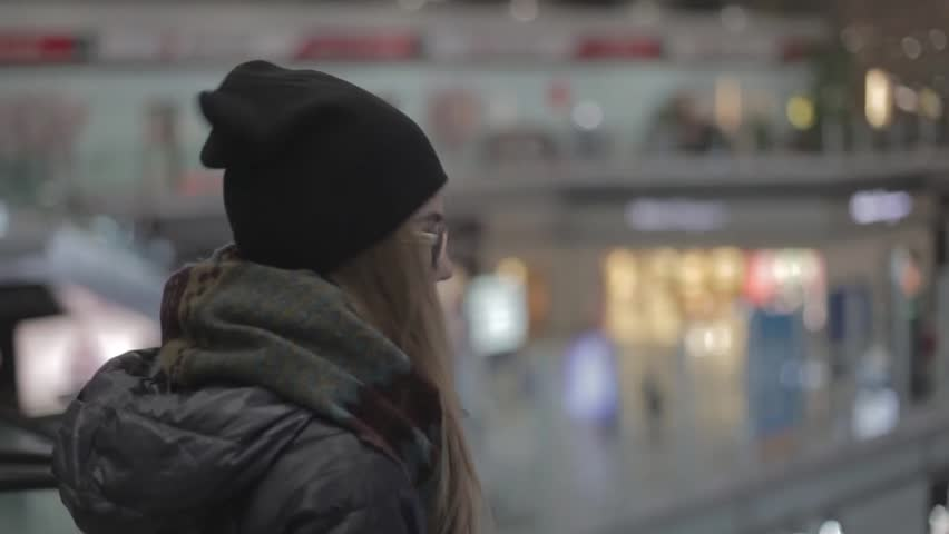 Young girl or teenager wearing glasses, in a scarf going down the escalator in the airport, holding her passport and ticket. She is late and a bit lost.Handheld tracking shot.