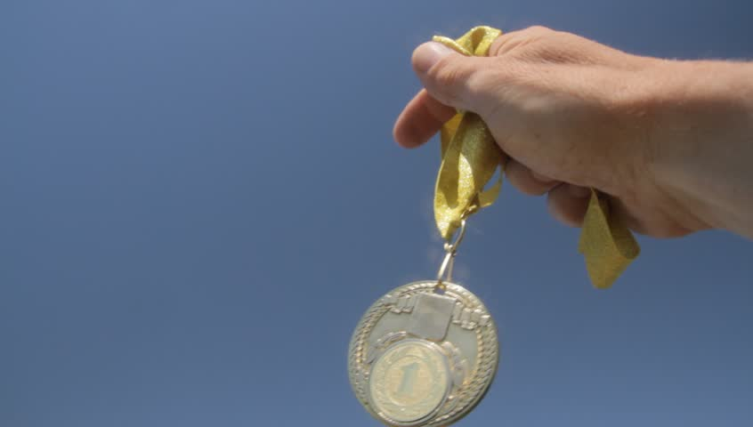 hand with a gold medal is raised to the top of the sun on a blue sky background
