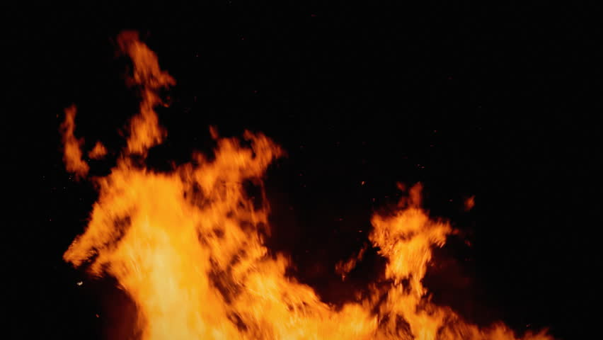 A bonfire of wooden branches burning in the dark. Detail of the flames, diegetic audio.