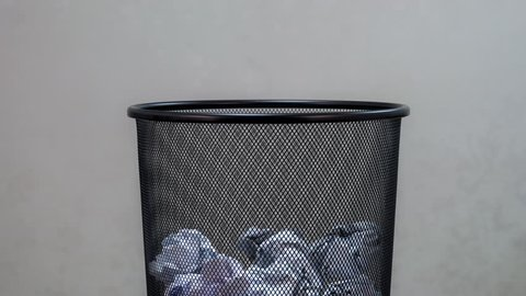 An empty office trash basket gets filled up with waste papers. Stop motion