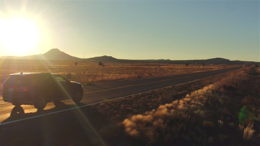AERIAL: Black SUV car driving along empty country road at golden summer sunset. People traveling, road trip on historic Route 66 through beautiful meadow desert scenery in sunny summer #16115923