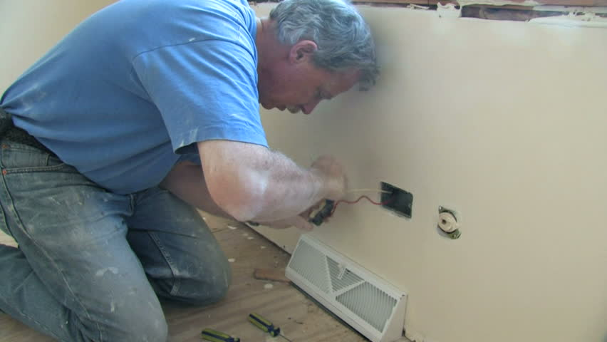Man installs an electrical outlet