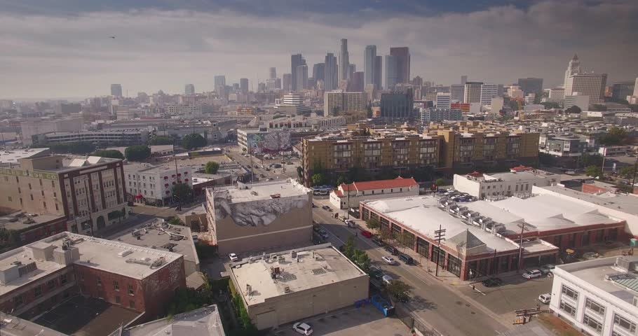 Aerial view of Arts district with downtown Los Angeles skyline in background. Camera flying forward. 4K UHD.