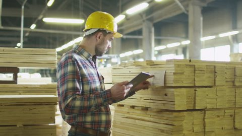 Worker counts wood stock using a tablet computer at a lumber factory warehouse. Shot on RED Cinema Camera in 4K (UHD).