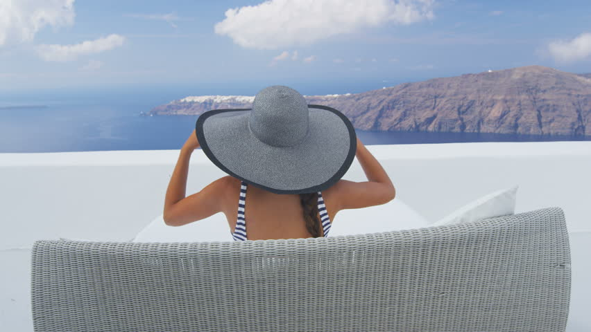 Vacation travel woman relaxing enjoying Santorini looking at famous view of Caldera. Young lady lying down on sun bed sofa lounge chair on holidays. Amazing view of sea. Europe tourist destination. | Shutterstock HD Video #16198213