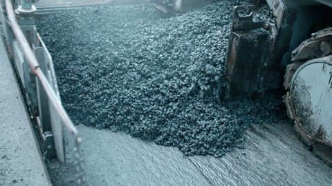 Asphalt paver machine during road construction, road construction crew apply asphalt layer