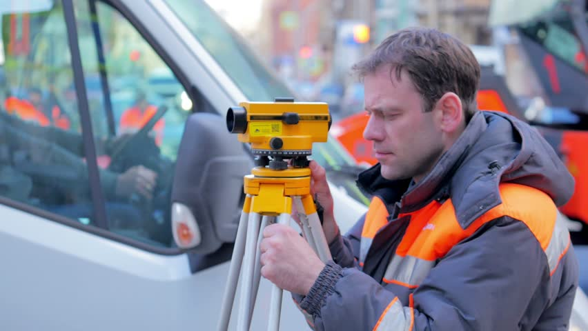 Engineers use tacheometer or theodolite for survey line in city centre, on a background of road works