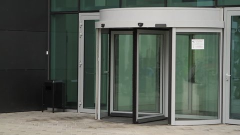 Business woman entering modern building with offices. Businesswoman entering revolving door.
