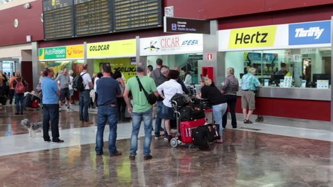 SOFIA REINA AIRPORT, TENERIFE, SPAIN \x97 CIRCA DEC, 2015: Stands of car rental companies are in arrival hall of south international airport of Tenerife island. People stand in queue for vehicles hire