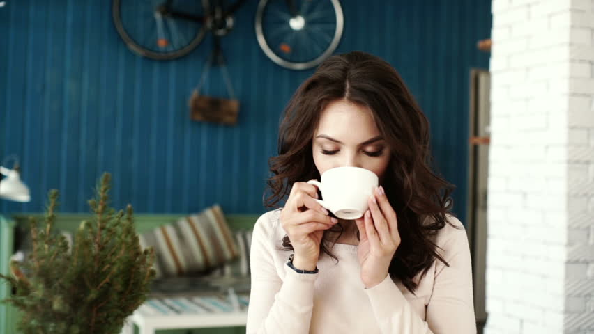 Happy girl drinking coffee and relaxing in cafe. Stylish makeup and hairstyle.