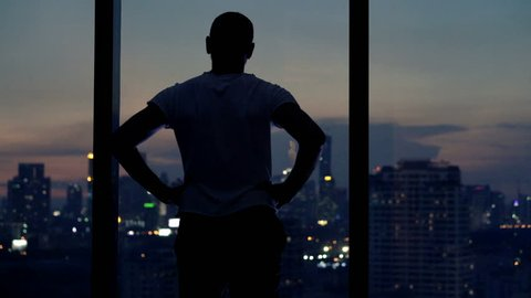 Young man admire view from window at home at night