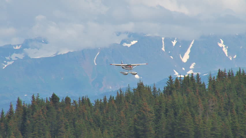 Descending from a cloudy sky with mountains in the background, a red and white floatplane lands on a lake with houses and other planes in the background.