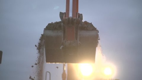 Bulldozer charging shovel with sand and transporting to pile, close up, excavator creating heap at  construction site. Separating ground. Slow motion shot in the dusk.
