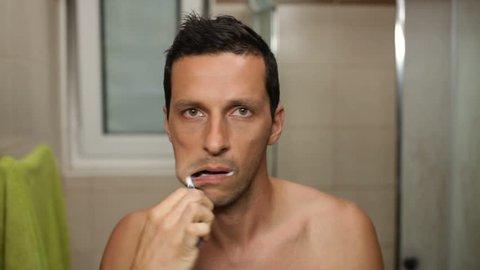 Shirtless man brushing his teeth.