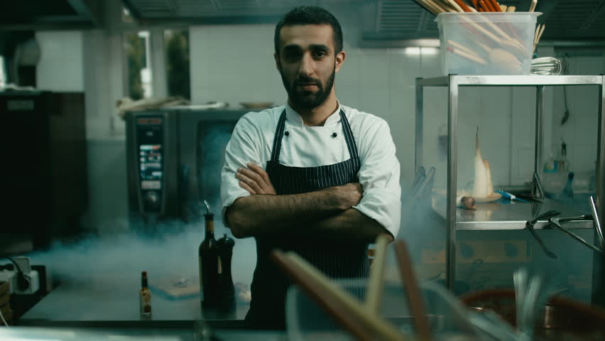 HD cinemagraph. Handsome Caucasian chef standing in the restaurant kitchen. Motion photo seamless loop. Blackmagic URSA Mini