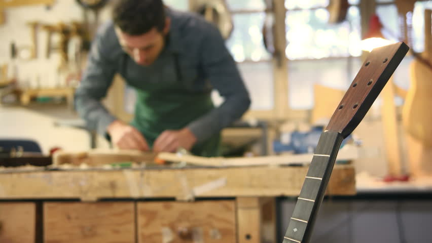 People and art, artisan work with mid adult man employed as craftsman in italian workshop with musical instruments, smoothing guitar body