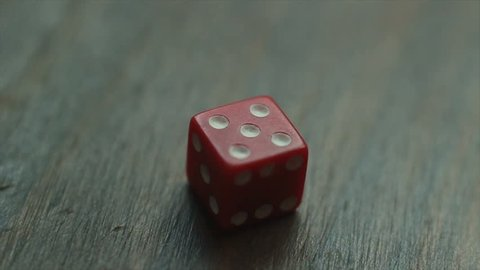 Red plastic die rolls on a wooden table, rolling all possible outcomes: one, two, three, four, five and six. Looped and easy to cut or extend.