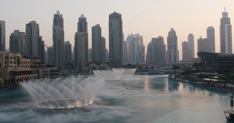 Singing fountains at sunset in Dubai downtown near the Burj Khalifa building