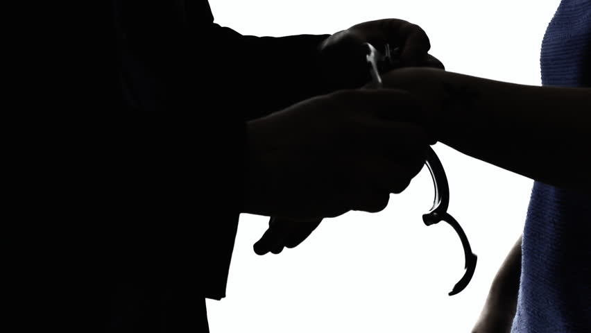 A woman freed from handcuffs from a male officer. Silhouette detail shot of the hands.