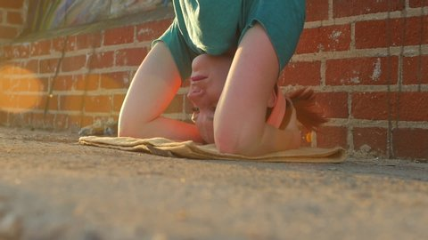 A young woman doing a headstand on the streets on an urban environment. - Slow Motion - Model Released - filmed at 96 fps - Clip is HD 1920 x 1080