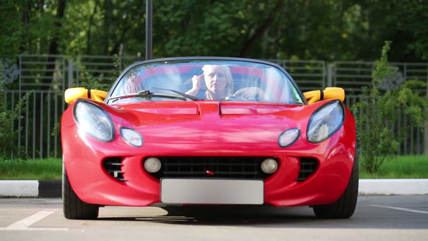 Blonde Woman Sits In Red Sport Car Looks In Mirror At Sunny Day   HD Stock Design Ideas