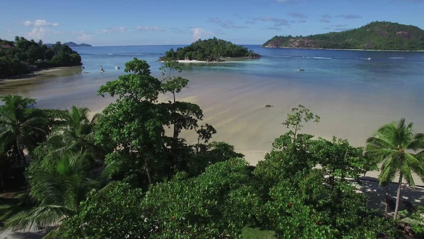 4k aerial video, bird eye view, drone fly over the Seychelles islands. Small tropical island. Islands in the ocean. Palm. Ocean. Sky. White sand. Beach. Waves. Island. Islands. Tropics.