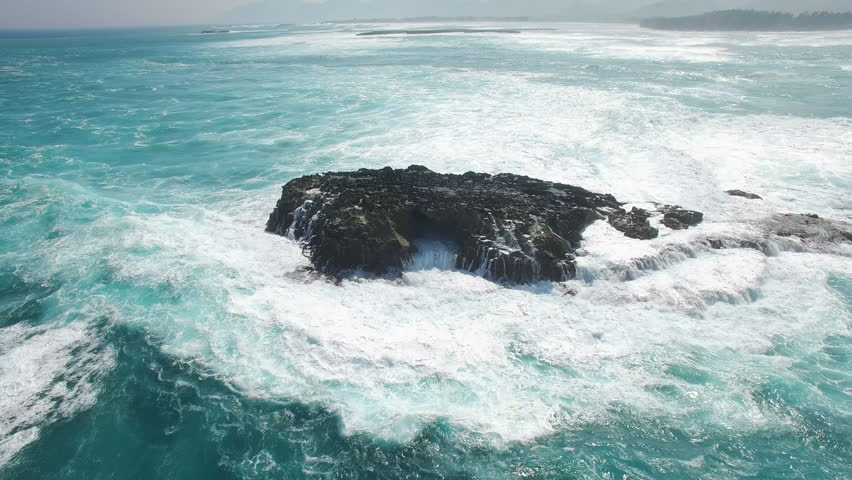 Aerial shot of ocean waves and cliff - waves washing up on a rock in sea