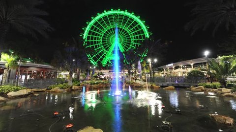 Time-lapse of 'The Orlando Eye' with a colored fountain in front. It is the largest observation wheel on the East Coast of Florida and located on International Drive in Orlando.