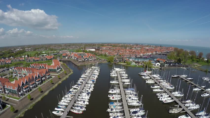 Aerial flying backwards over the recreational harbor of Volendam showing recreational boats ships and typical dutch traditional homes great tourist attraction Holland for traditional clothing 4k