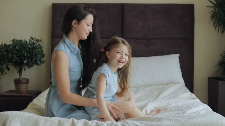 Mother combing daughter hair on bed at home