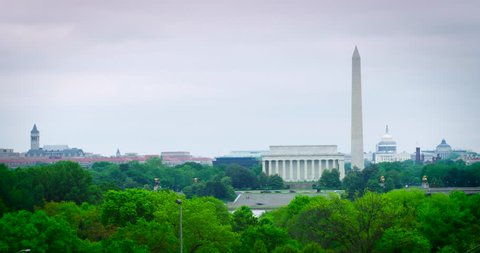 Washington DC Monuments Timelapse Wide Shot Cloudy Spring Day with green trees. The Old Post Office/Trump Hotel, Lincoln, Washington, US Capitol. Use the 4K to do a digital zoom. Available in HDR.