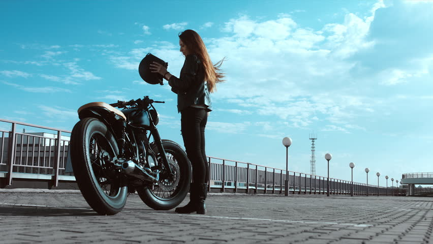 Young sexy Caucasian female putting on helmet near her custom cafe racer motorcycle. 60 FPS slow motion. Blackmagic URSA Mini