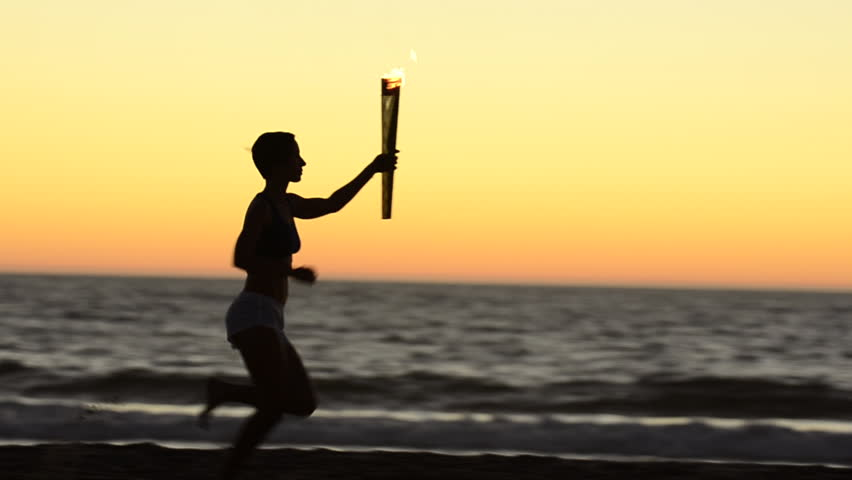 Woman running with a simulated Olympics torch on the beach at sunset. - Model Released - 1920x1080 - Full HD