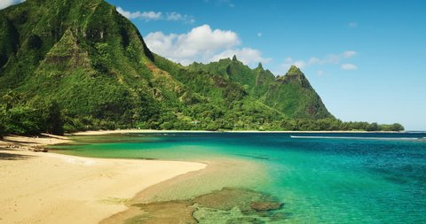 Aerial view flying over amazing white sand beach and tropical coral reef lagoon towards beautiful green mountains on Kauai