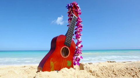 Vacation travel concept with ukulele and lei on tropical beach Oahu. Hawaii. Traditional Hawaiian instrument and flower wreath or garland on perfect sandy beach on Oahu.
