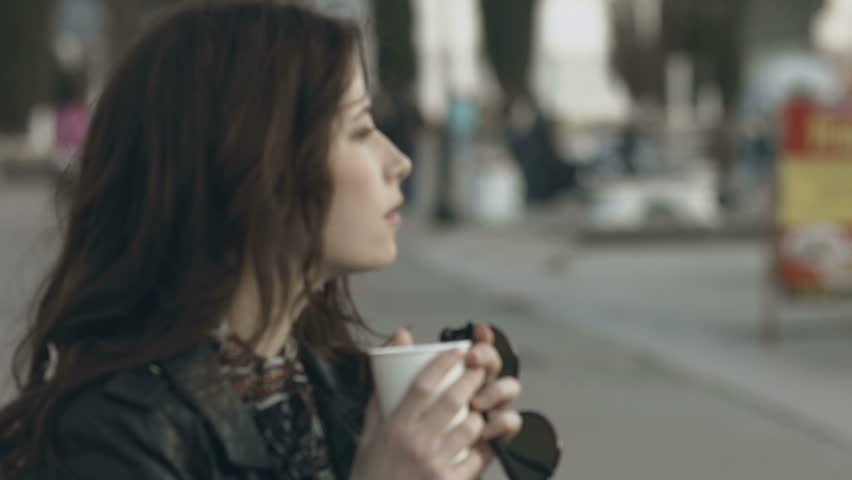 Girl in a dress and a leather jacket walks with a cup of coffee in the city | Shutterstock HD Video #16642300