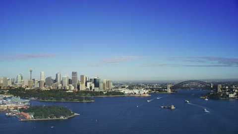 Aerial Sydney Harbour approaching the Harbour Bridge and Sydney Opera House on a beautiful clear sunny blue day.