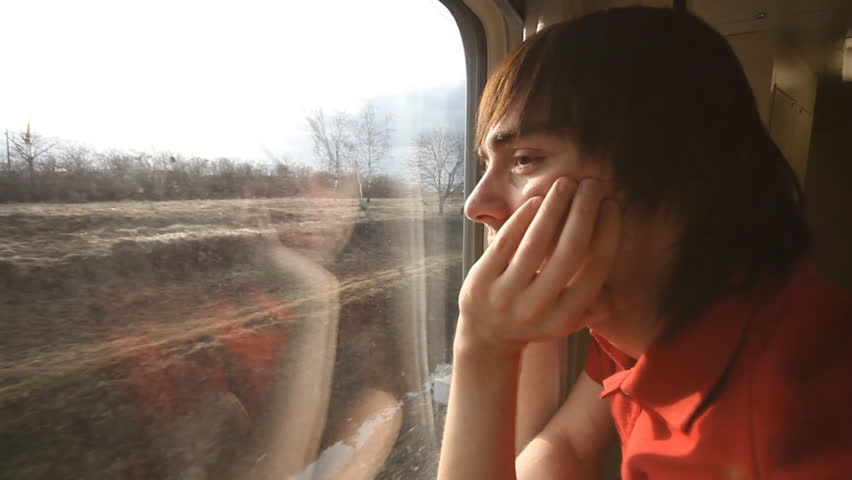 man riding a passenger train and looks out the window