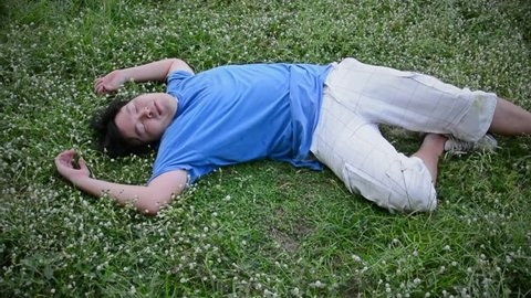 An Asian Thai guy drop dead on the grassy ground with his face turn up in HD