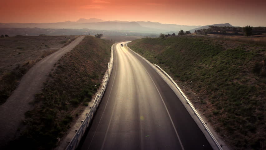 Aerial shot of car passing on the highway to the mountains | Shutterstock HD Video #1672807