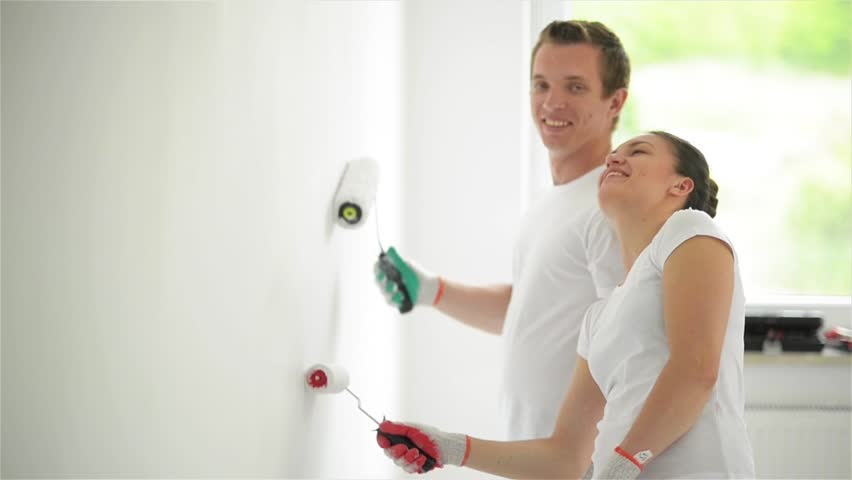 Young couple decorate their new apartment. Young husband and wife are painting the wall. Beautiful couple making repairs in their new flat.   Shutterstock HD Video #16777732