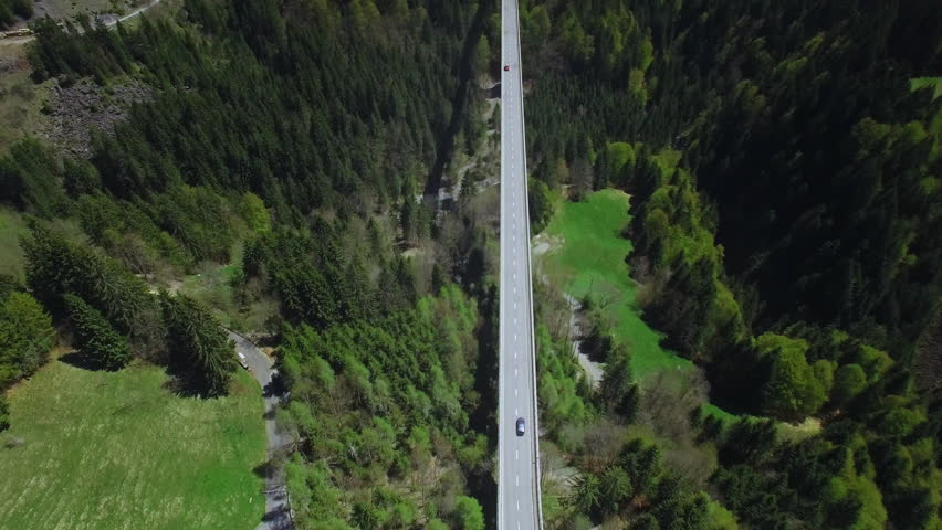 4K Car commercial aerial shot / Following a car on a bridge - surrounded by nature and forests