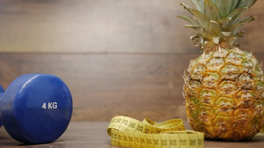 Diet weight loss fitness health care concept with measure tape, pineapple, water bottle, fitness dumbbell, fitness tracker bracelet. Pineapple, metric ribbon on wood background. Diet heathy lifestyle.