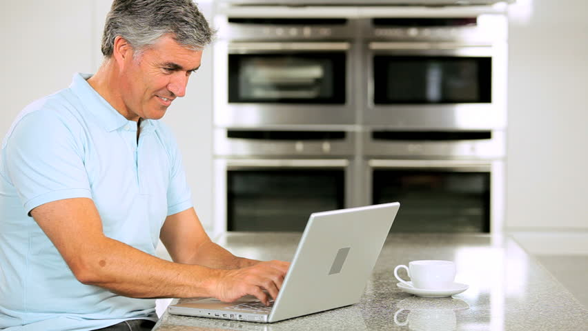 Middle Aged Male with Laptop on Kitchen Counter