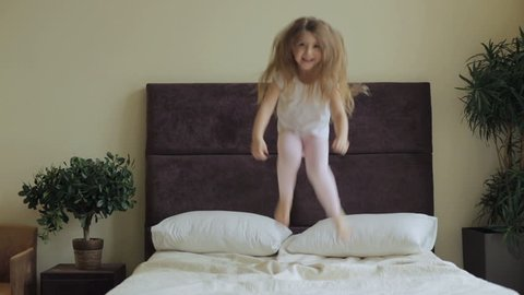 A beautiful little girl in a white T-shirt and pink pantyhose, cuddles on the big bed and fooling around.