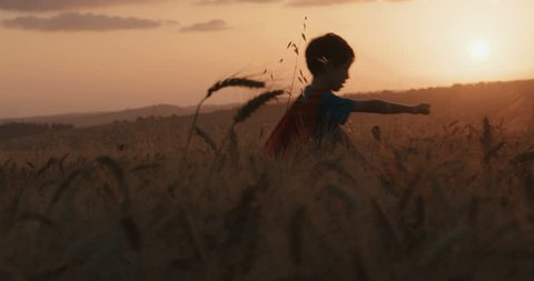 Boy with a super hero cape runs in a field during sunset