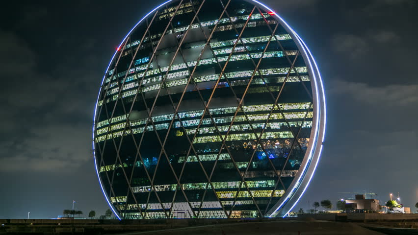 ABU DHABI, UAE - JANUARY 16: The Aldar headquarters building night timelapse is the first circular building of its kind in the Middle East in Abu Dhabi, UAE. Cloudy sky
